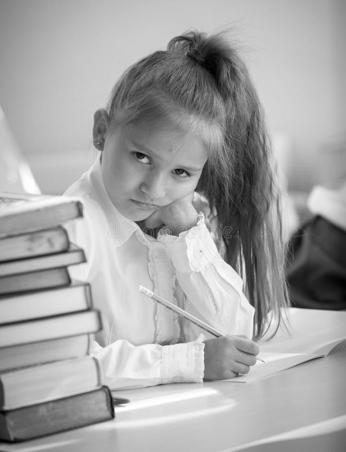 Monokrom stående av den upprivna flickan som gör läxa royaltyfria bilder