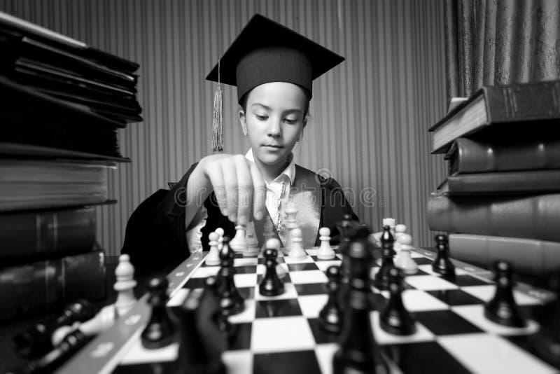 Monokrom stående av flickaavläggande av examenhatten som spelar schack arkivbild