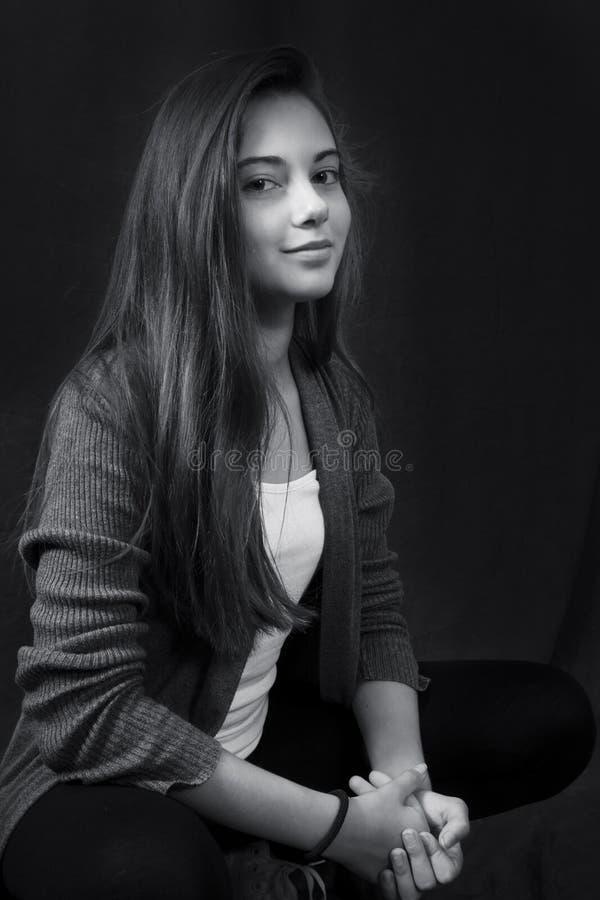 Monokrom stående av ungt härligt flickasammanträde royaltyfri fotografi