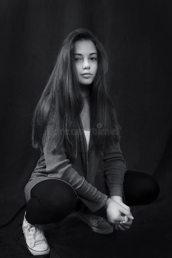 Monokrom stående av ungt härligt flickasammanträde arkivbild