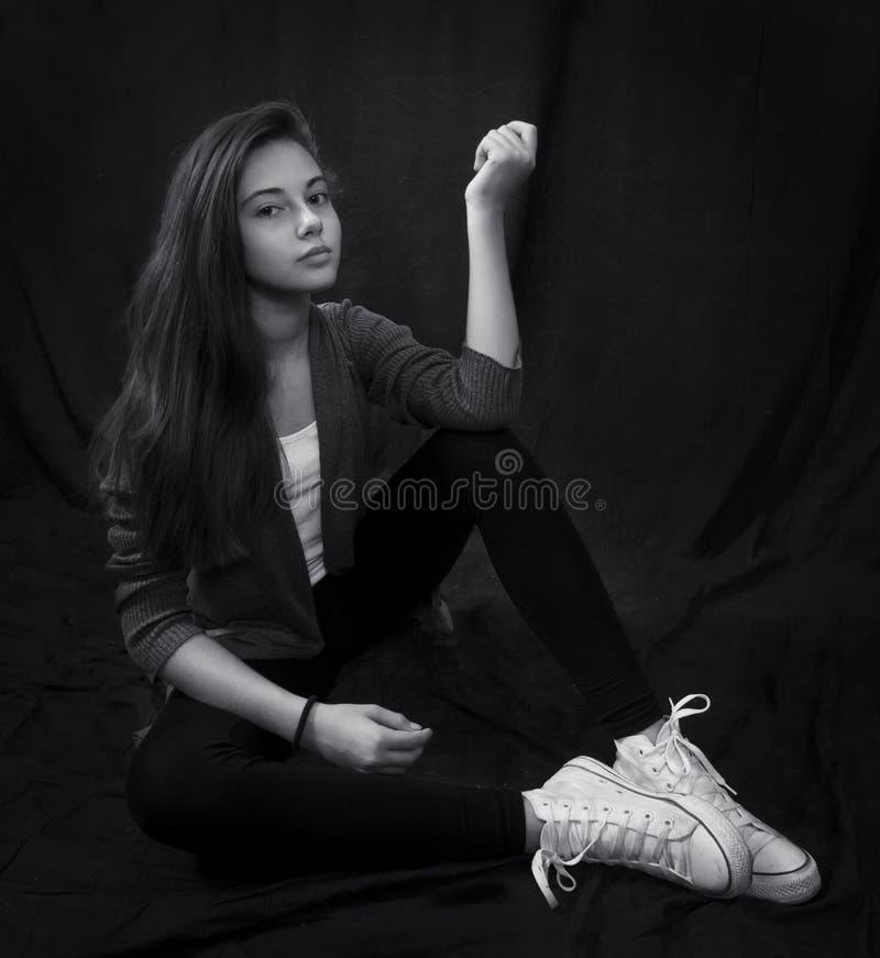 Monokrom stående av ungt härligt flickasammanträde arkivfoton