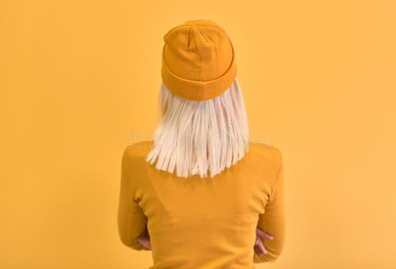 Monokrom stående för bakre sikt av den nätta kvinnan för blont hår som bär gul kläder, med korsade händer som ser den tomma vägge arkivbild