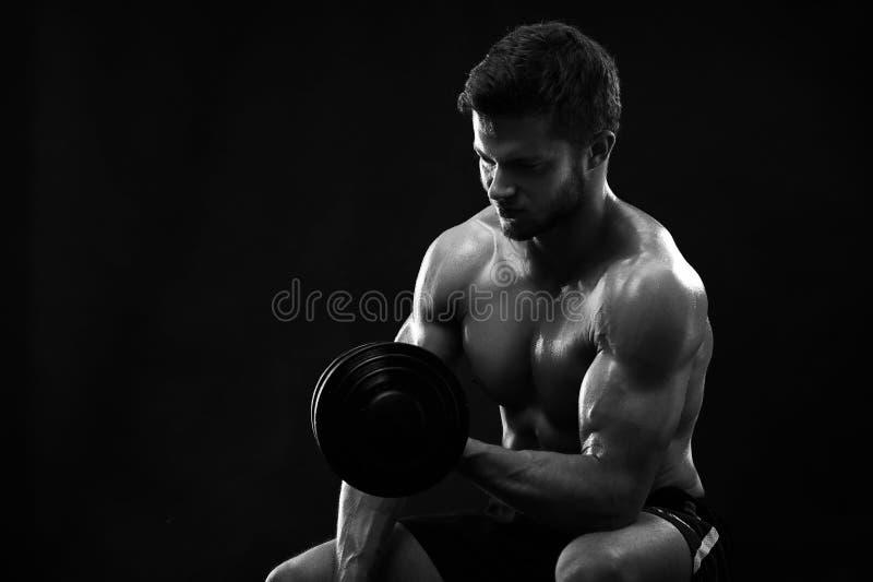 Monokromskott av en idrotts- riven sönder ung idrottsman med dumbb royaltyfria bilder