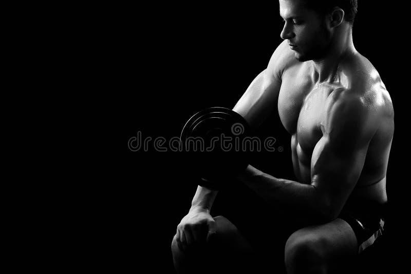 Monokromskott av en idrotts- riven sönder ung idrottsman med dumbb royaltyfri foto