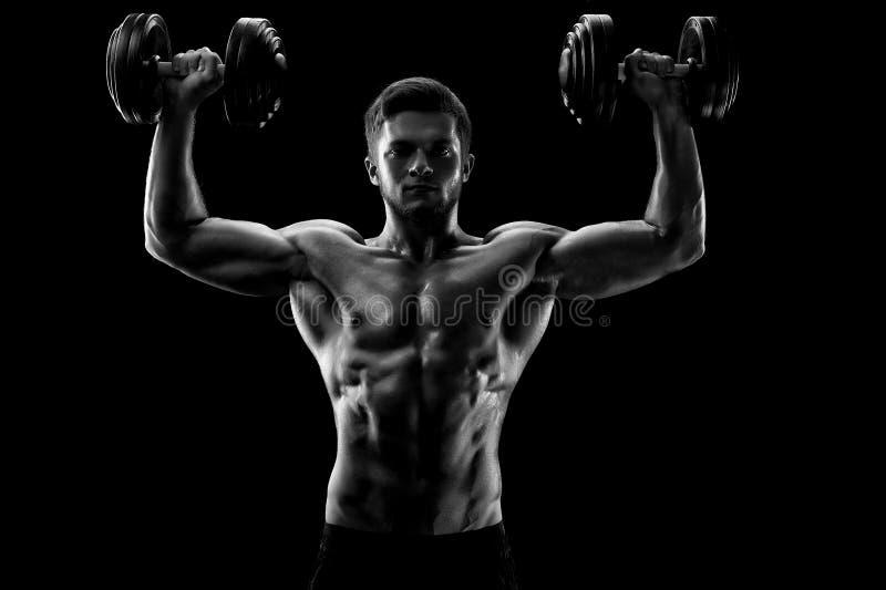 Monokromskott av en idrotts- riven sönder ung idrottsman med dumbb arkivbild
