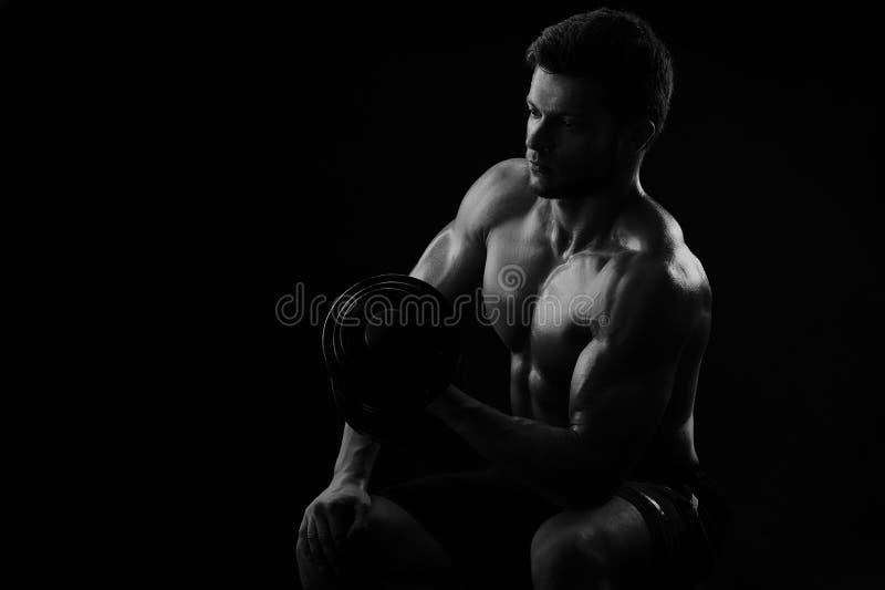 Monokromskott av en idrotts- riven sönder ung idrottsman med dumbb royaltyfria foton