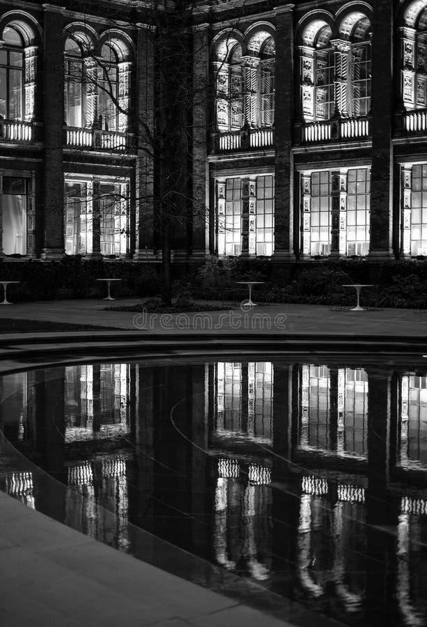 Monokromt foto av den theJohnMadejski trädgården på Victoria och Albert Museum som fotograferas på natten med reflexion i vattnet royaltyfria foton