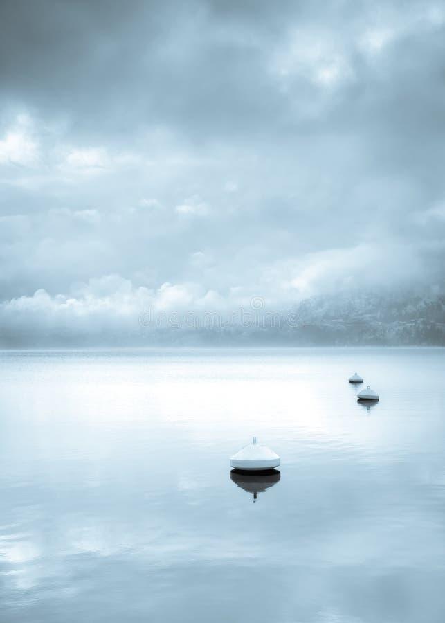 Monokromt landskap av boj som svävar i den lugna sjön med för vinterstorm för vatten reflekterande moln och dimma med berget i av royaltyfri foto