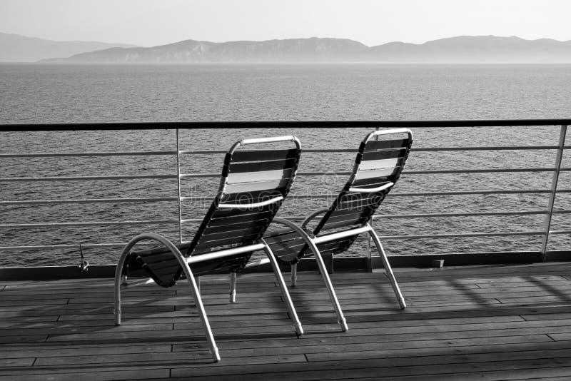 Monokromt svartvitt foto av två tomma obesatta ensamma Deckchairs som ut ser till havet royaltyfri bild