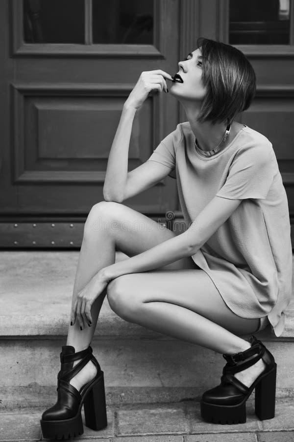 Monokromt utomhus- fullt kroppfoto av den unga härliga trendiga damen som poserar på trappa Modell som bär stilfull kläder arkivfoton