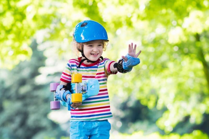Monopatín del montar a caballo del niño en parque del verano foto de archivo libre de regalías