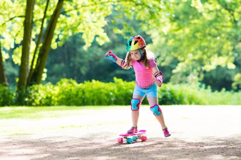Monopatín del montar a caballo del niño en parque del verano fotos de archivo