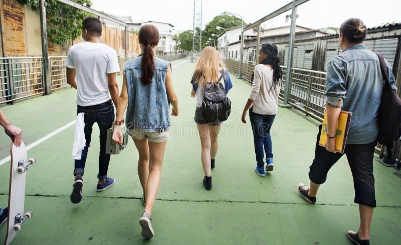 Monopatín que camina Yout de la vista posterior de la unidad de la amistad de la gente fotografía de archivo libre de regalías