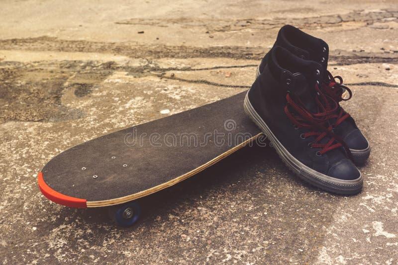 Monopatín y zapatos en el suelo concreto imagenes de archivo