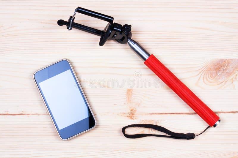 Monopod et téléphone sur le bureau en bois photo stock