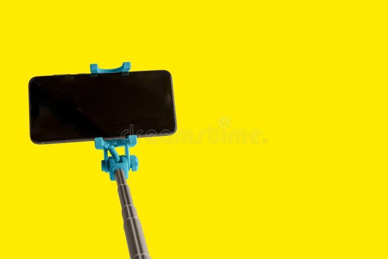 Monopod para el selfie con el teléfono elegante Palillo de Selfie con smartphone aislado en fondo amarillo imágenes de archivo libres de regalías