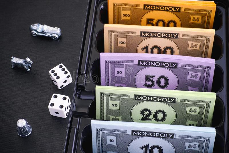 Monopol-Brettspielkasten mit Geld verpackt, Zeichen und würfelt stockbilder