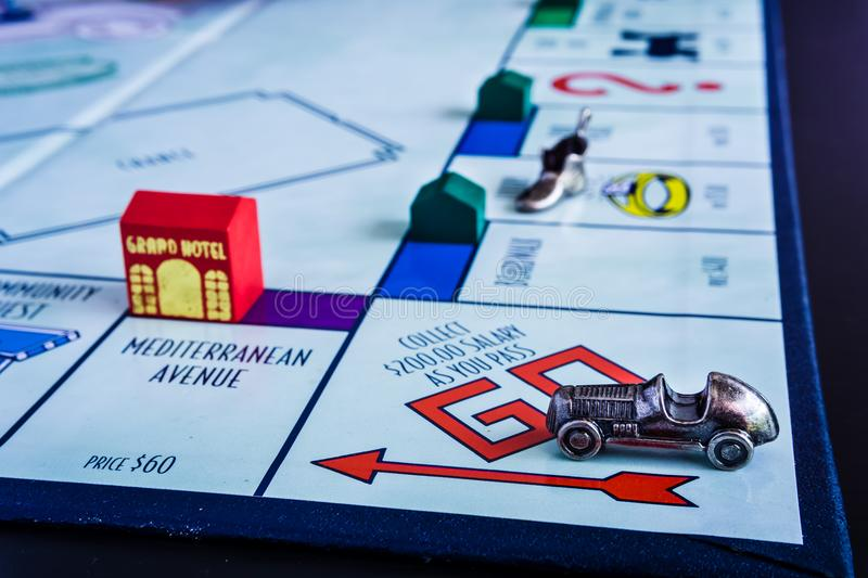 Monopoly Board Game with another play closing up. Monopoly Board Game close up with the car passing the GO. The classic real estate trading game from Parker stock image
