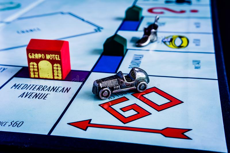 Monopoly Board Game with another play closing up. Monopoly Board Game close up with the car passing the GO. The classic real estate trading game from Parker royalty free stock photos