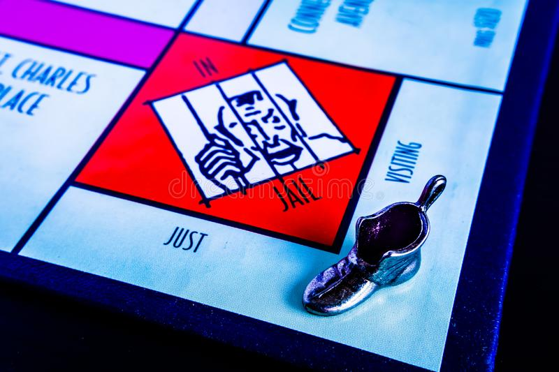 Monopoly Board Game - Boot Token Visiting Jail. Monopoly Board Game close up with the boot token just visiting jail. The classic real estate trading game from stock images