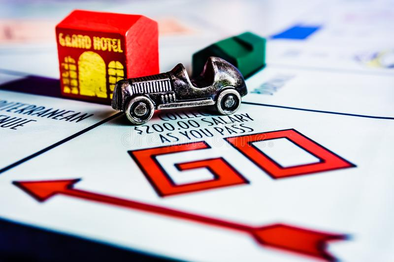 Monopoly Board Game - Car Passing GO Box. Monopoly Board Game close up with the car passing GO box. The classic real estate trading game from Parker Brothers was royalty free stock image