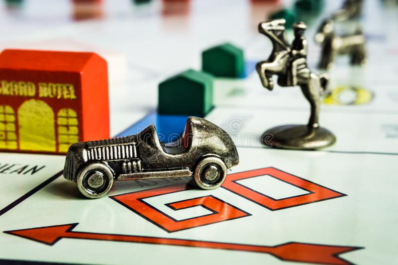 Monopoly Board Game - Car token followed closely by other tokens. Monopoly Property Trading board game from Parker Brothers. The classic real estate trading game royalty free stock photography