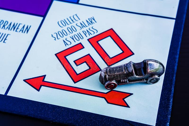 Monopoly Board Game - Car Token passing GO box. Monopoly Board Game close up with the car token passing the GO. The classic real estate trading game from Parker royalty free stock images