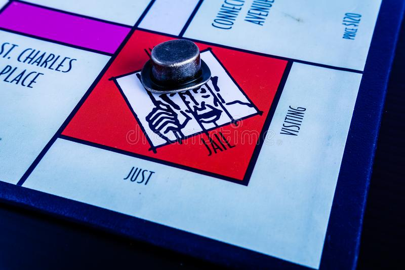 Monopoly Board Game - Hat Token in Jail. Monopoly Board Game close up with the hat token in jail. The classic real estate trading game from Parker Brothers was royalty free stock photos