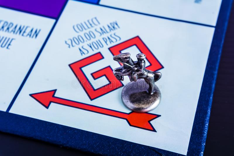 Monopoly Board Game - Horse Token passing GO. Monopoly Board Game close up with the horse token passing the GO. The classic real estate trading game from Parker royalty free stock image