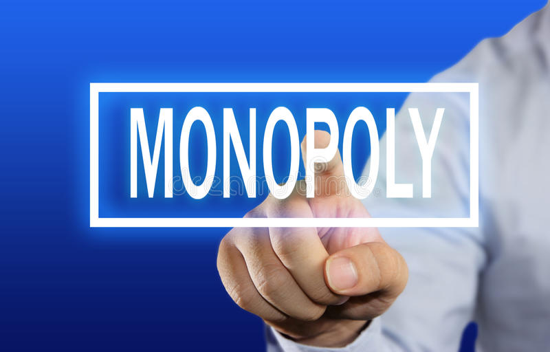 Monopoly Concept. Business concept image of a businessman clicking Monopoly button on virtual screen over blue background royalty free stock photo