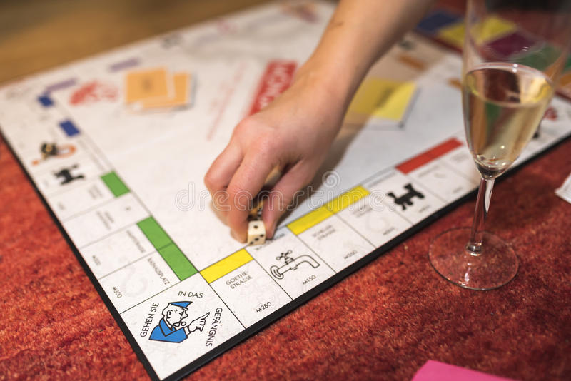 Monopoly game. Hand grabbing the dice of a Monopoly game, German edition royalty free stock photos