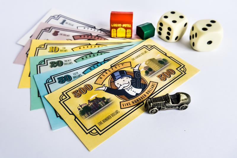 Monopoly Board Game - Money, Dices, House and Car. Monopoly Property Trading board game from Parker Brothers. The classic real estate trading game from Parker royalty free stock image