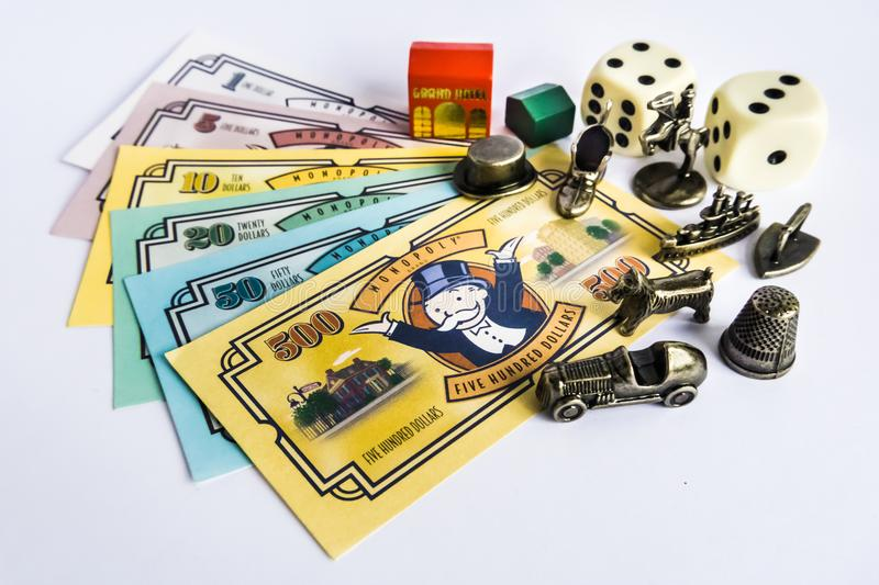 Monopoly Board Game - Money, tokens, dices and house. Monopoly Property Trading board game from Parker Brothers with money, tokens, dices and house on table. The royalty free stock photography