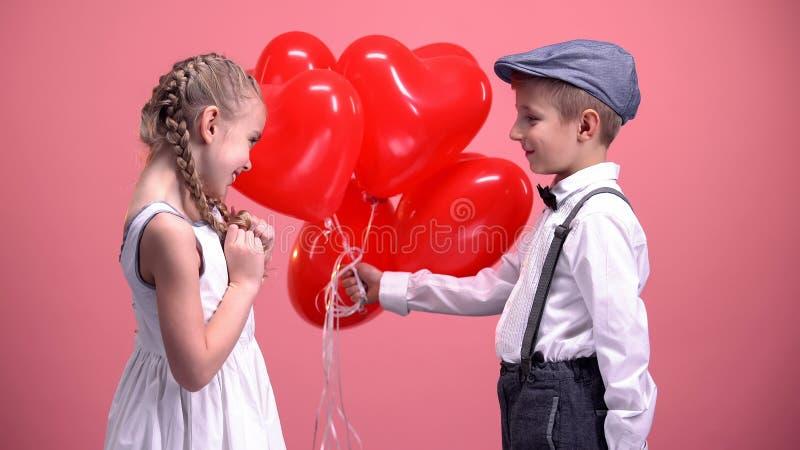 Monsieur mignon donnant à fille mignonne les ballons en forme de coeur, surprise de jour de valentines image libre de droits