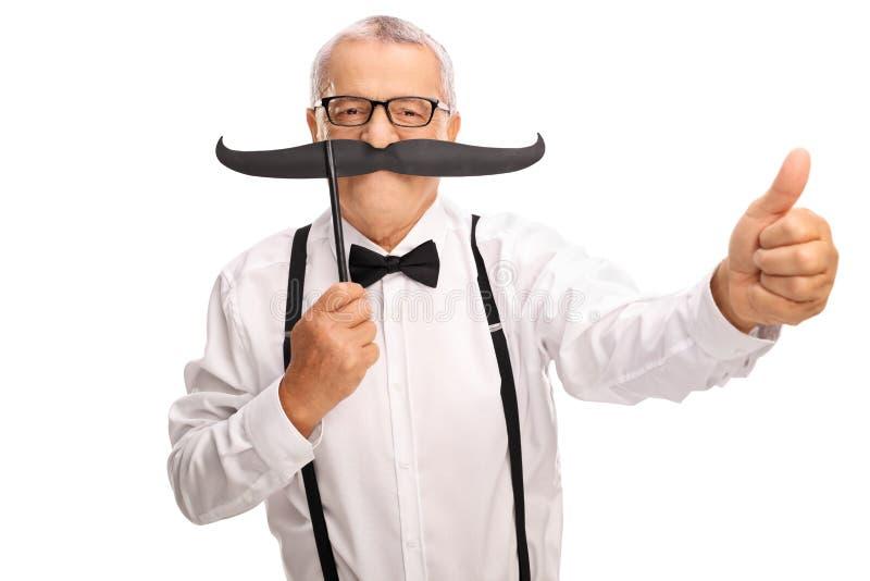 Monsieur plus âgé avec la grande fausse moustache et un pouce  photographie stock libre de droits