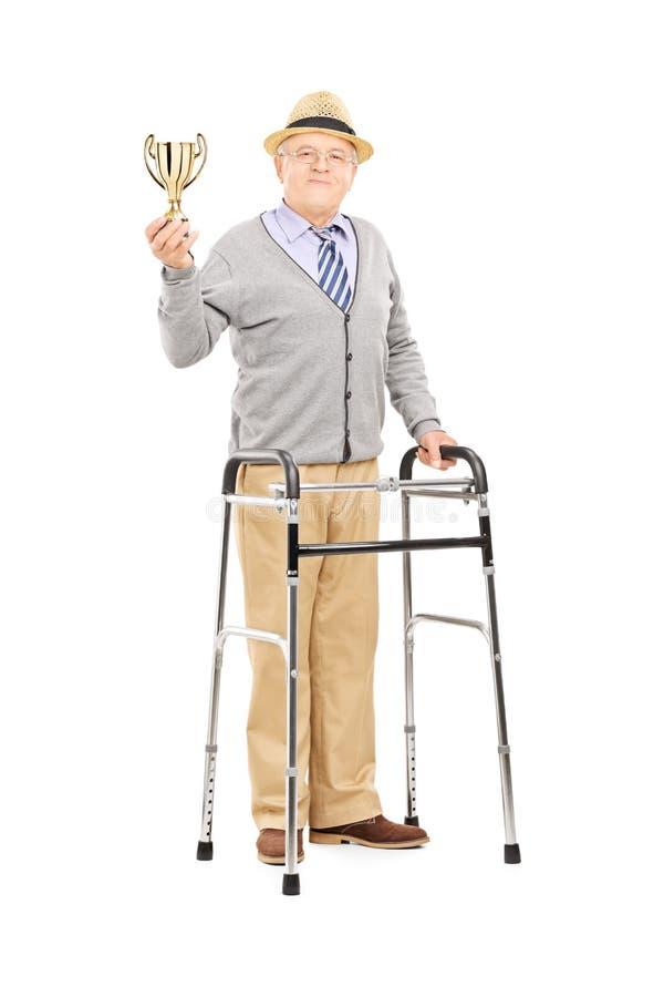 Monsieur plus âgé avec le marcheur tenant une tasse d'or images libres de droits