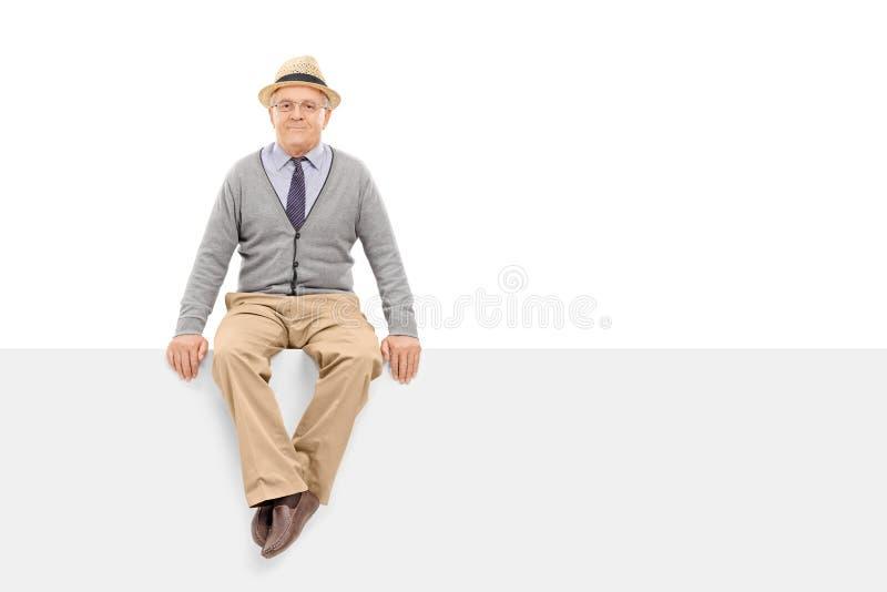 Monsieur supérieur s'asseyant sur un panneau d'affichage vide images libres de droits