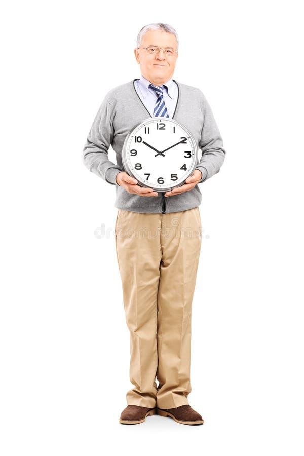 Monsieur supérieur tenant une grande horloge murale image libre de droits