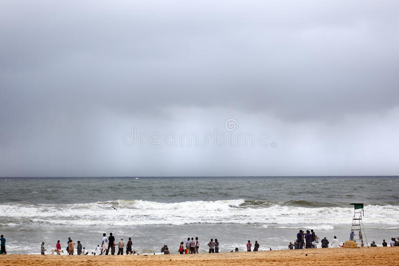 Monsoon. Calangute, India-August 31, 2012.While Indian tourists enjoy the beach, on the horizon is the torrential rains of the monsoon will soon come to the stock photos