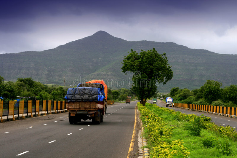 Monsoon season. A truck travelling along the highway towards a mountain covered with dark monsoon clouds stock photo