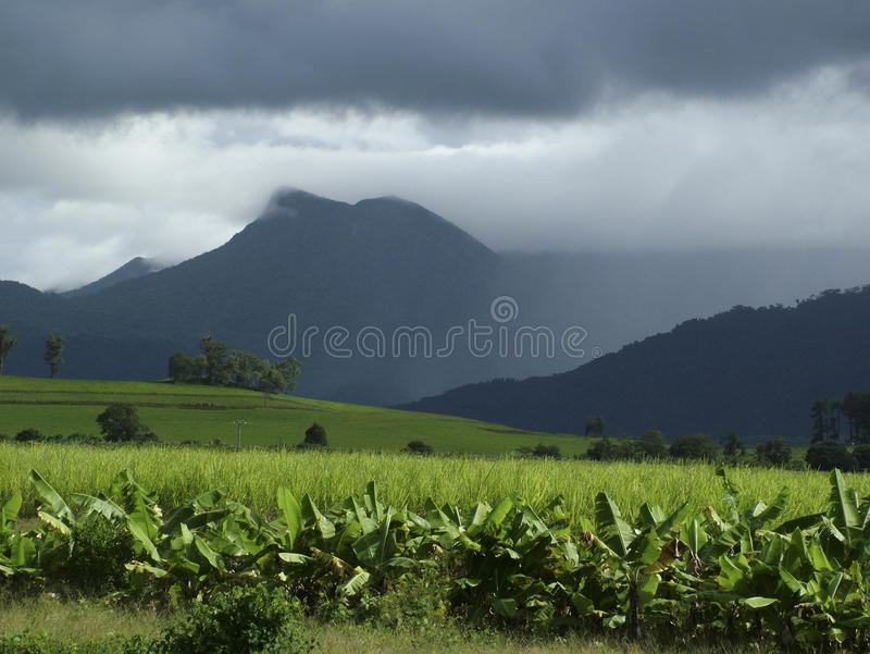 Monsoon storm. Over mountains with banana and sugarcane plantation in sunshine stock image