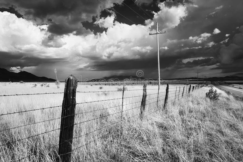 Monsoon storm in Sonoita, Arizona. Black and white landscape of the desert grasslands with fence and power royalty free stock photos