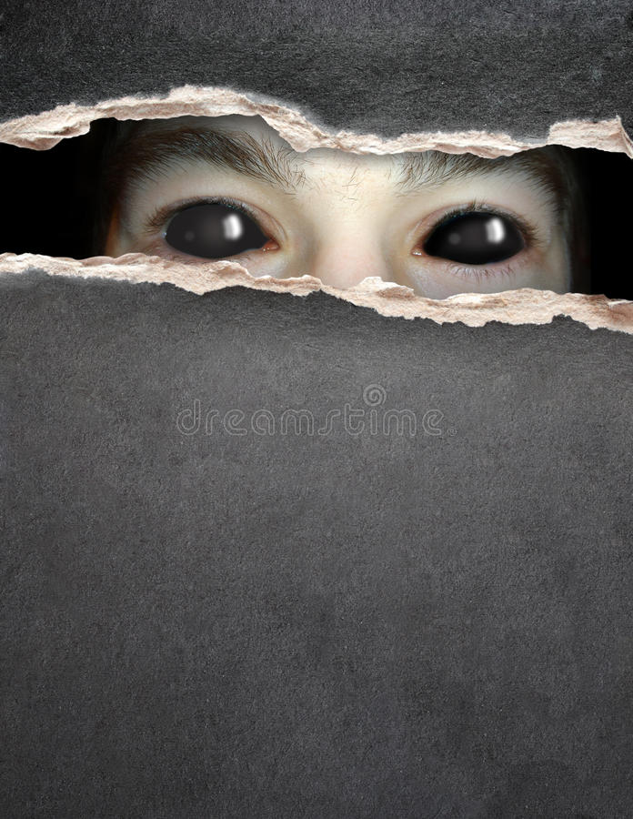 Monster eye in hole in the paper. Dark series - a look from darkness. Monster eye in hole in the paper stock photo