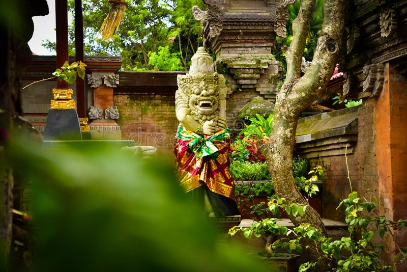Stone statue of god guarding sacred temple with colorful traditional cloting. Monster god guarding entrance of sacred temple and royal palace in romantic Ubud stock photo
