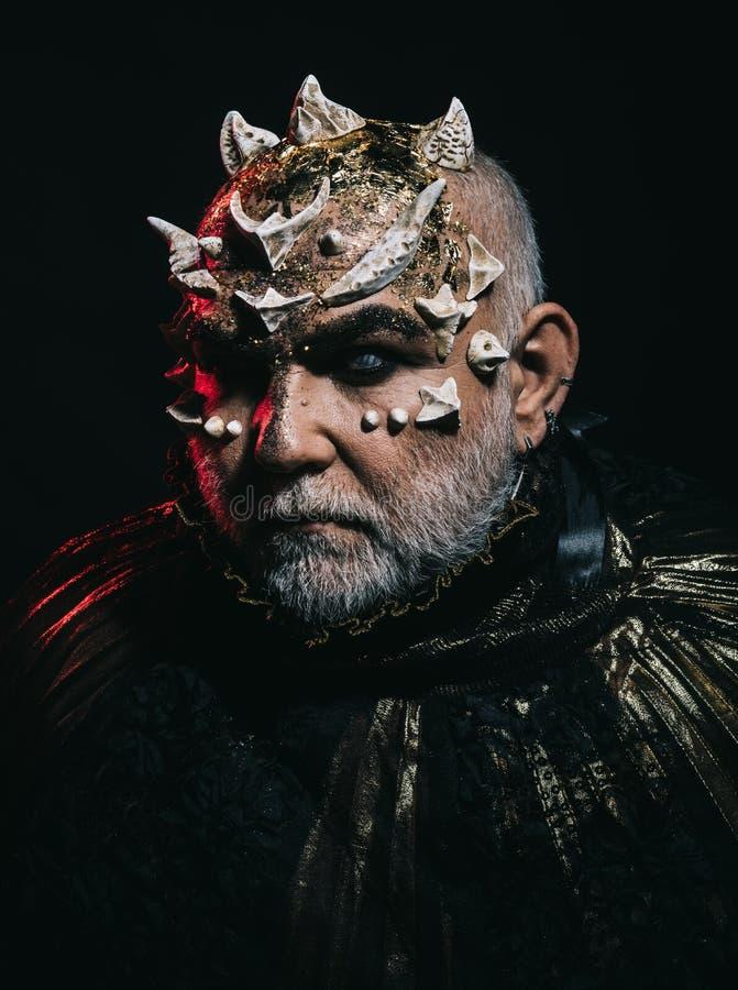 Monster met doornen op hoofd en gloeiende gouden die huid op zwarte achtergrond wordt geïsoleerd Bejaarde met witte baard met stock afbeeldingen
