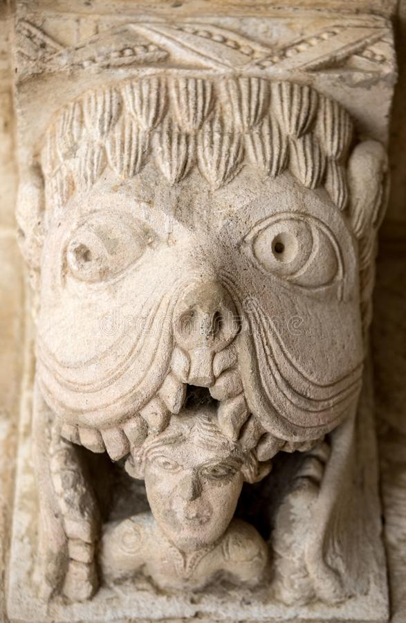 Monster or Tarasque Devouring a Sinner c12th Romanesque Carving in the Cloisters Montmajour Abbey near Arles. Provence France royalty free stock photo
