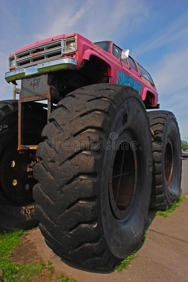 Monster Truck Car Bigfoot with Giant Front Wheel. Retired Monster Truck Car Bigfoot in Pink color with Giant Front Wheel on Display outside of Restaurant royalty free stock images