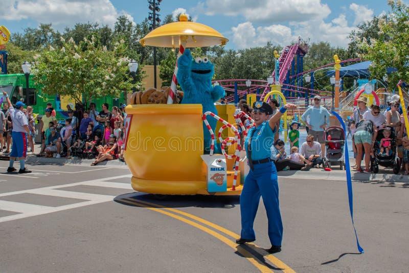 Monstro da cookie no flutuador e na mulher coloridos da polícia na parada do partido do Sesame Street em Seaworld fotografia de stock royalty free