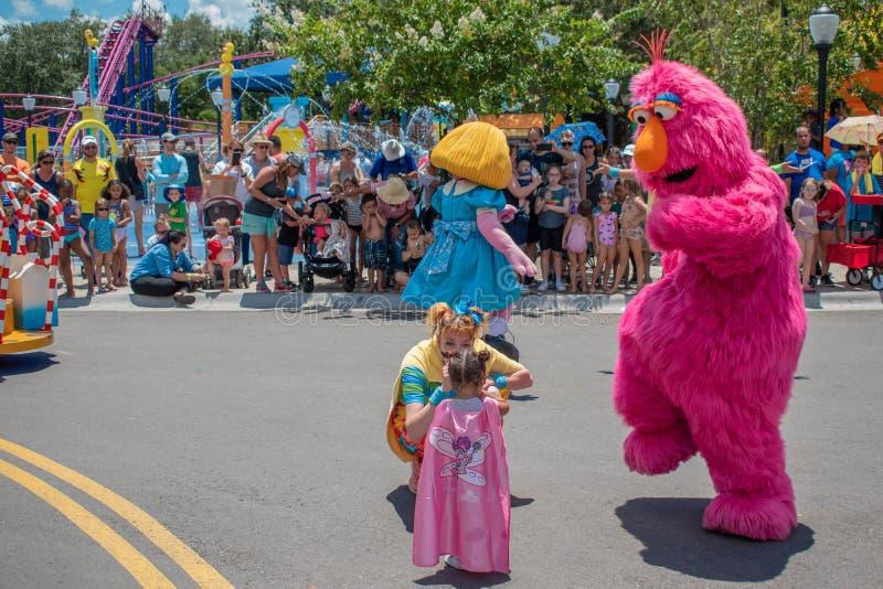 Monstro do alvorecer, da televisão da pradaria, mulher do dançarino e menina na parada do partido do Sesame Street em Seaworld 2 fotos de stock