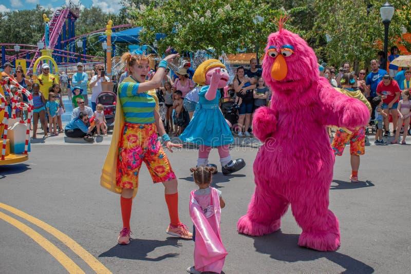 Monstro do alvorecer, da televisão da pradaria, mulher do dançarino e menina na parada do partido do Sesame Street em Seaworld 1 imagens de stock royalty free